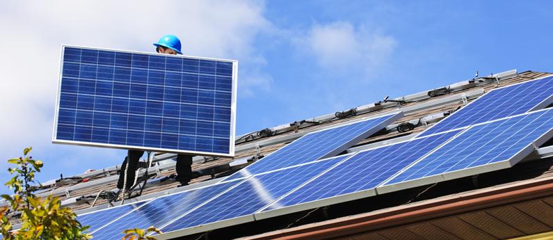 Een installateur plaatst zonnepanelen op een dak.