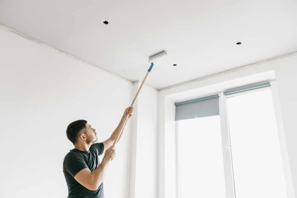 schilder verft plafond met verfstok